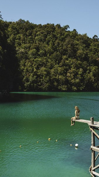 Sugba lagoon in Siargao with emerald green water and girl in biking on a diving board